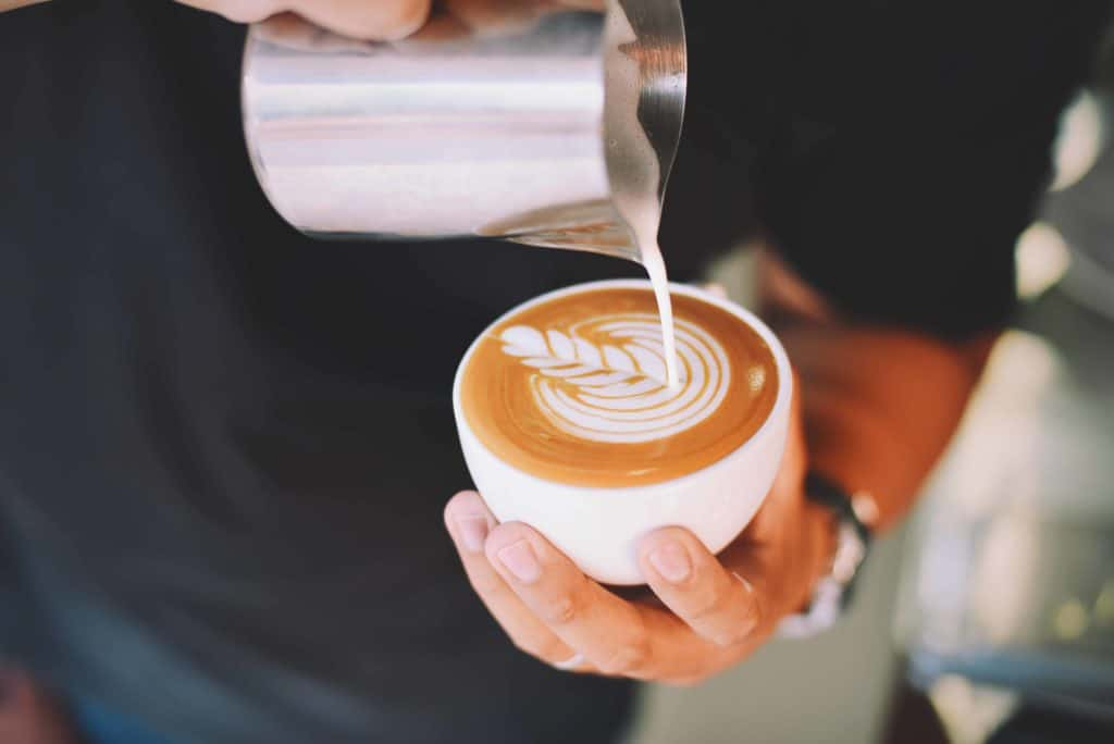 close up of hand holding cappuccino 302901 compressed
